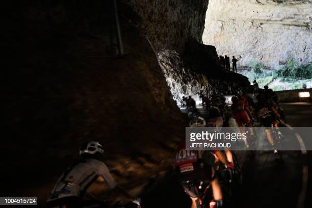 The pack rides through a natural cave during the 16th stage of the 105th edition of the Tour de France cycling race between Carcassonne and...