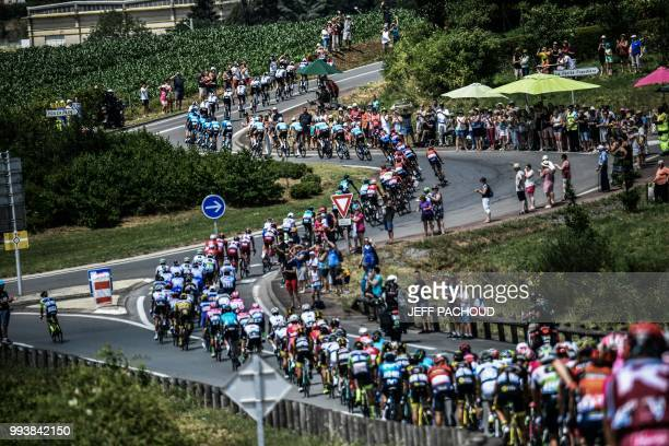 TOPSHOT The pack rides through a roundabout during the second stage of the 105th edition of the Tour de France cycling race between...