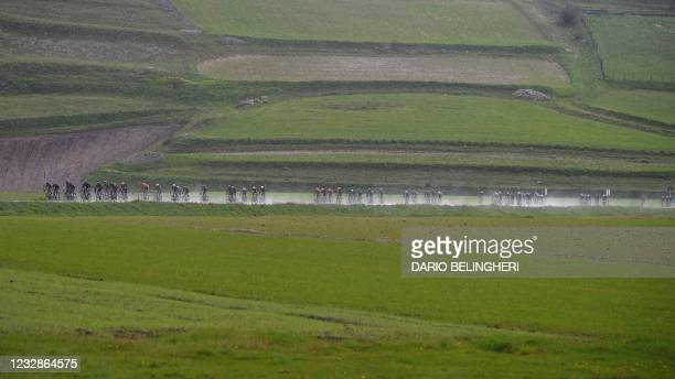 The pack rides under the rain near Castelluccio di Norcia during the sixth stage of the Giro d'Italia 2021 cycling race, 160 km between Grotte di...