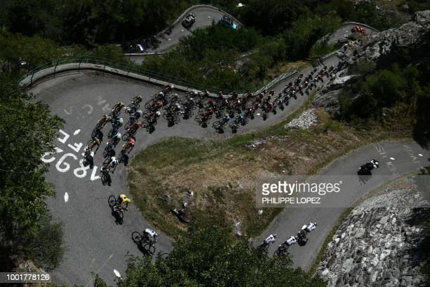 TOPSHOT The pack with Great Britain's Geraint Thomas wearing the overall leader's yellow jersey ascends the Montvernier bends during the twelfth...