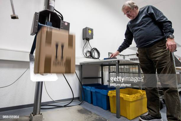The packaging examiner Uwe Moeller testes a package by dropping it on the ground at the package check station of the German Post in Darmstadt Germany...