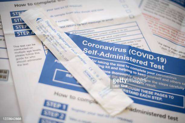 The packaging from a disposable oropharygeal swab sampler and the instructions from a COVID-19 self-administered test kit provided by the Department...