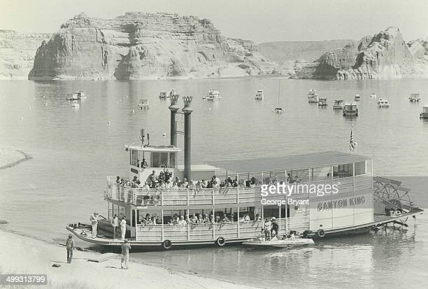The paddlewheeler Canyon King unloads passengers on the shores of Lake Powell a manmade ocean that gleams like a blue jewel amidst the red rock of...