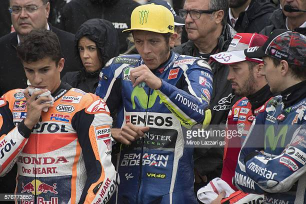 The paddock family pray in pit during the minute of silence in memory of those who lost their lives in Nice before the MotoGP race during the MotoGp...