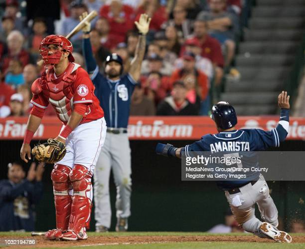 The Padres' Alexi Amarista scores past Angels' catcher Carlos Perez on a Justin Upton single in the seventh inning Wednesday night at Angel Stadium...