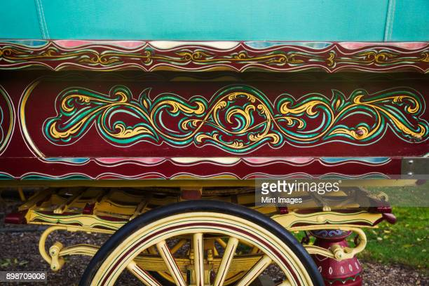 the painted decorated side panel of a bow top gypsy caravan and large wooden wheel. - gypsy caravan stock pictures, royalty-free photos & images