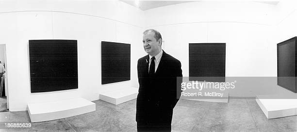 The painter Ad Reinhardt stands in a gallery during an exhibiton of his abstract paintings at the Museum of Modern Art possibly during the 'Americans...