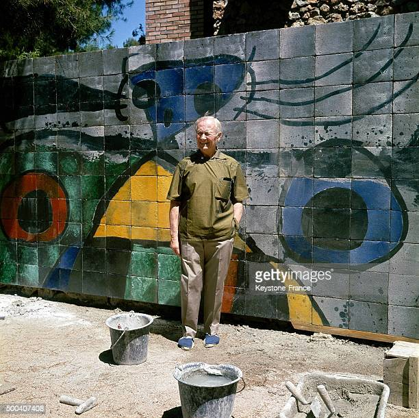 The painter engraver sculptor and ceramic artist Joan Miro in front of one of his works a ceramic mural fresco in his garden on July 18 1968 in...