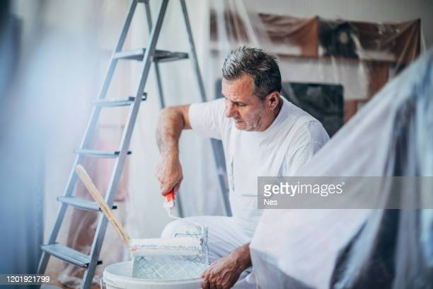 the painter prepares paint for the decoration of the apartment - artist stock pictures, royalty-free photos & images