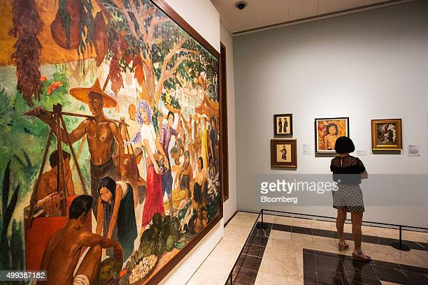 The painting 'Market at Marmot' by artist Louis Rollet left hangs on display as a visitor looks at other works at the National Gallery Singapore in...