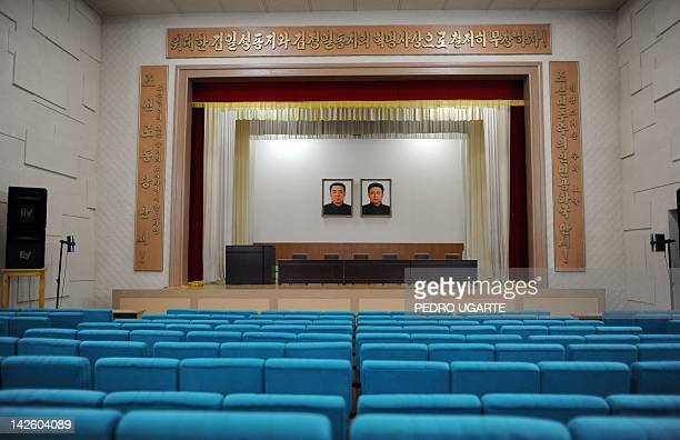 The painting of North Korean's late presidents Kim IlSung and his son Kim JongIl hang in an auditorium of a textile factory in Pyongyang on April 9...
