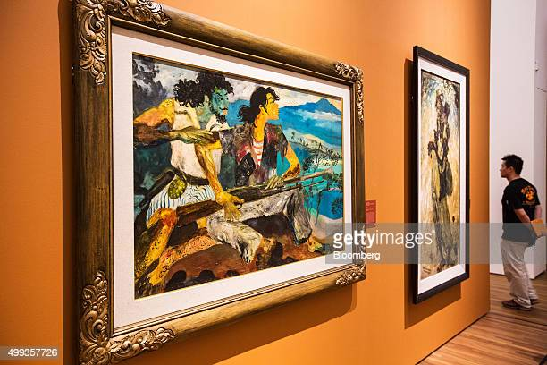 The painting 'War And Peace' by artist Hendra Gunawan left hangs on display as a visitor walks through the National Gallery Singapore in Singapore on...