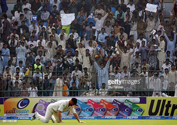 The Pakistan crowd celebrate as another four is notched up as England fielder Andrew Flintoff is grounded during the first day of the First Test...