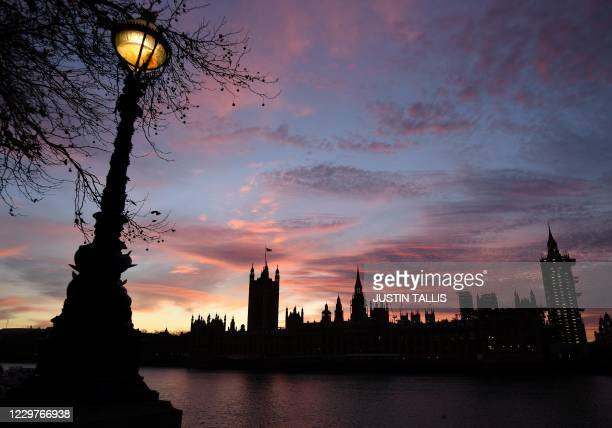 The Palace of Westminster, comprising both houses of parliament, the House of Commons and the House of Lords, is silhouetted in the late autumn sun...
