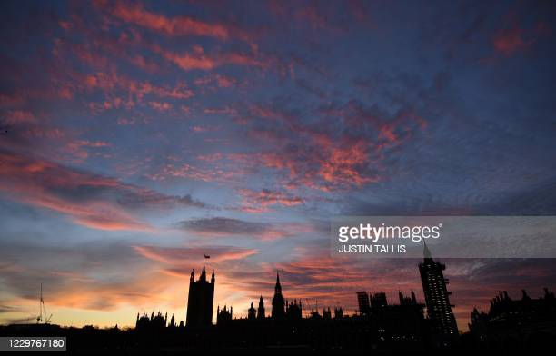 The Palace of Westminster, comprising both houses of parliament, the House of Commons and the House of Lords, is silhouetted by the setting sun in...