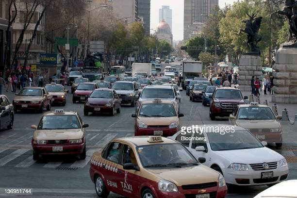 The Palacio de Bellas Artes stands in the background as traffic moves along Juarez Avenue in Mexico City Mexico on Thursday Jan 12 2012 Signs the...