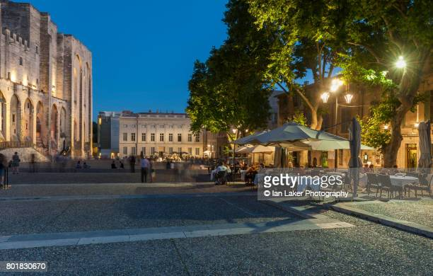 The Palais des Papes or Papal Palace at night with cafe tables, Avignon, Provence-Alpes-Côte d'Azur, France.