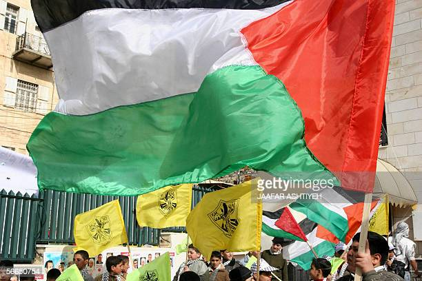 The Palestinian flag and yellow ruling Fatah party flags are held high during a Fatah rally in the northern city of Nablus 23 January 2006 on the...