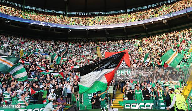 The Palestinian flag is waved by fans during the UEFA Champions League Playoff First leg match between Celtic and Hapoel BeerSheva at Celtic Park on...