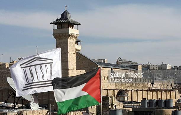 The Palestinian Rehabilitation Committee raised the UNESCO flag next to the national Palestinian flag in front of Hebron's Ibrahimi Mosque or the...