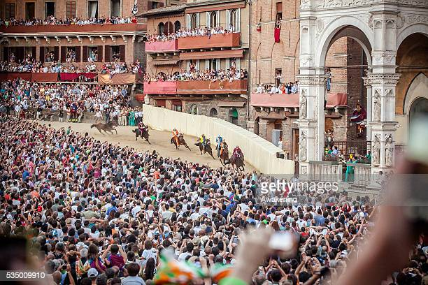 The Palio di Siena is a horse race that is held twice each year on July 2 and August 16 in Siena Italy Ten horses and riders bareback and dressed in...