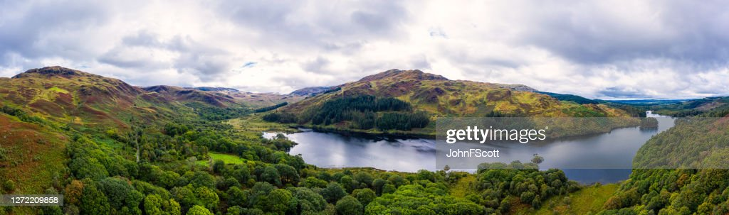 The panoramic aerial view from a drone of a Scottish loch and woodland in Dumfries and Galloway on an overcast day : Stock Photo
