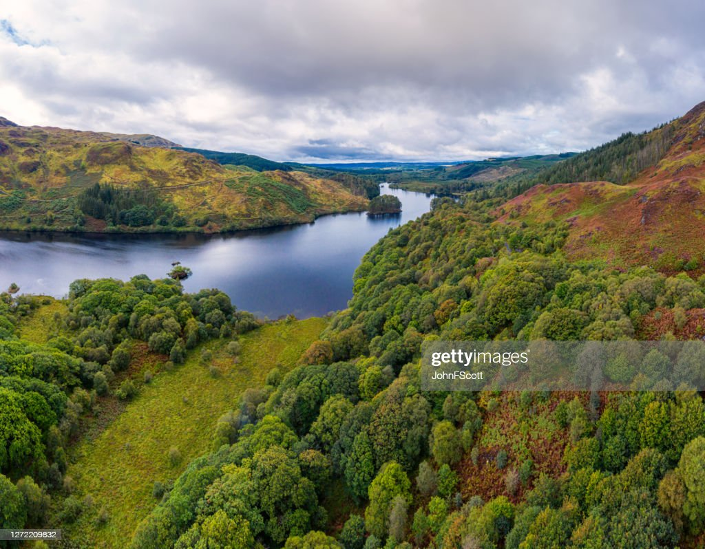 The panoramic view from a drone of a Scottish loch and woodland in Dumfries and Galloway on an overcast day : Stock Photo