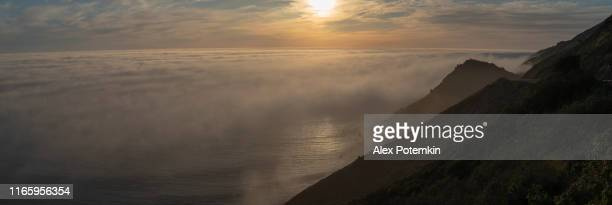 the panoramic view of the sunset over the low clouds forming over the pacific ocean. the view from a high point above clouds, in the mountains nearby big sur, cabrillo highway, californian west coast, usa. the high-resolution extra-wide stitched panorama. - ecossistema imagens e fotografias de stock