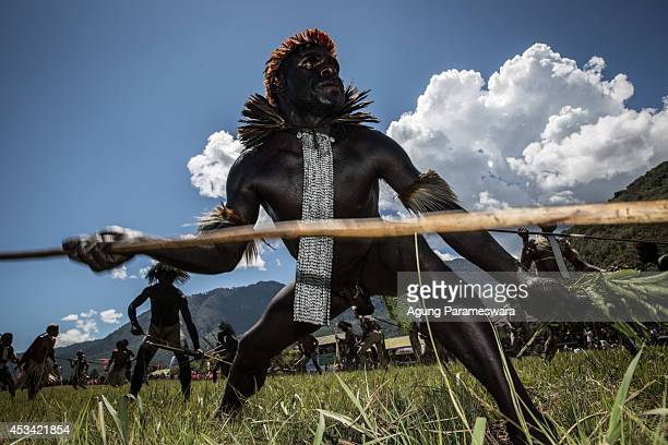 The Papuanese tribal men perform mock battles in an open field during the 25th Baliem Valley festival on August 8, 2014 in Wamena, Indonesia. The...