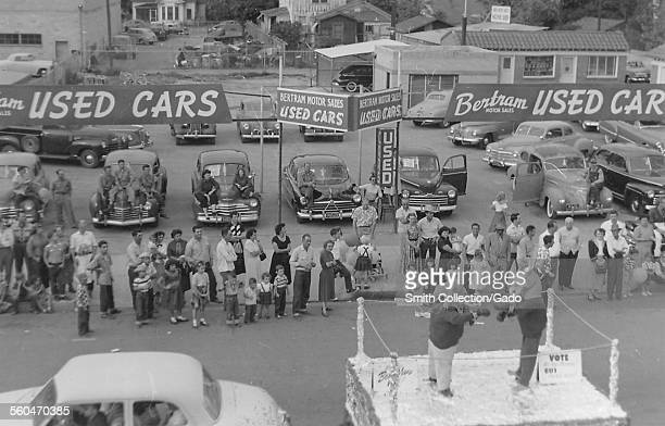 The parade and floats passing large crowds on the road the Delano harvest holiday parade California 1950