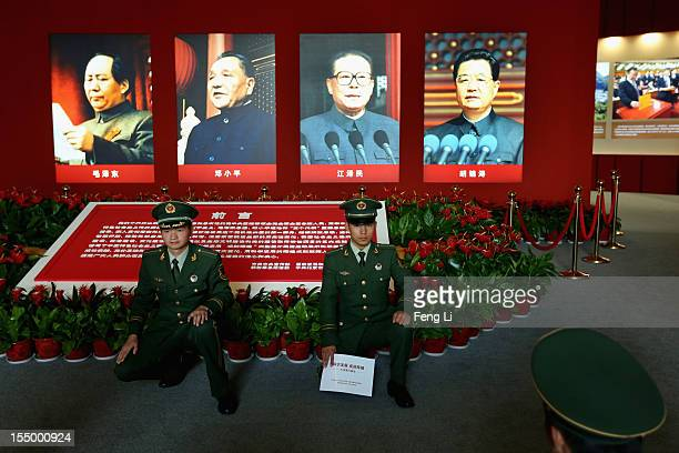 The paramilitary policemen pose for photo in front of the portraits of China's President Hu Jintao and former President Jiang Zeming as visiting an...
