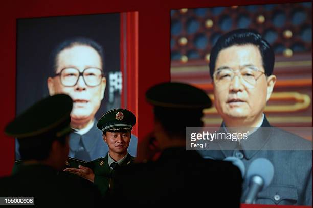 The paramilitary policemen pose in front of the portraits of China's President Hu Jintao and former President Jiang Zeming as visiting an exhibition...