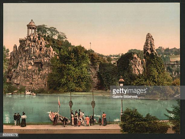 The Parc des Buttes Chaumont in northeastern Paris with the Belvedere of Sybil on the rocky peak at the left and a bridge on the right circa 1900 A...
