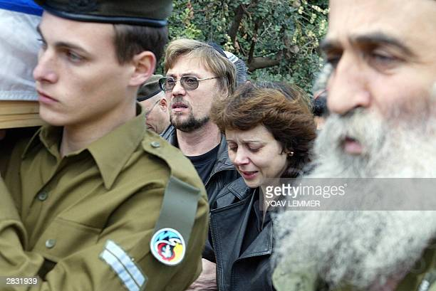 The parents of killed Israeli female soldier Angelina Shchirov 26 December 2003 mourn during her funeral at the Kfar Saba cemetery as they follow her...