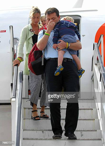 The parents of missing toddler Madeleine McCann Kate and Gerry carry their twoyearold twin children Sean and Amelie as they arrive back in Britain...