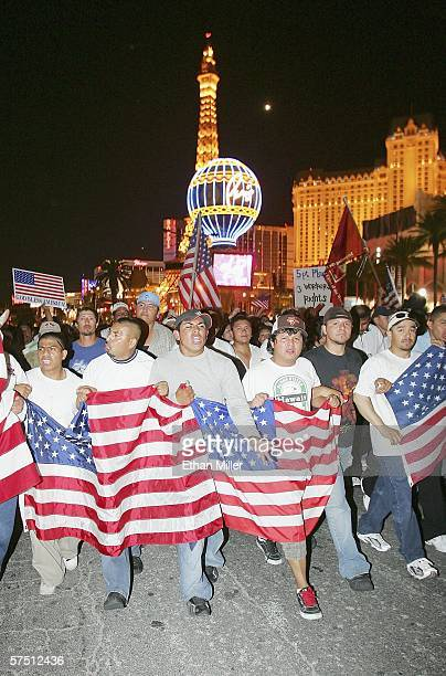 The Paris Las Vegas is seen behind people marching down the Las Vegas Strip in support of immigrant rights as part of a Day Without Immigrants on May...