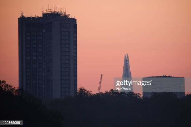 The Park Lane Hilton hotel and Shard skyscraper rise beyond the trees of Hyde Park at dawn in London, England, on September 22, 2020.