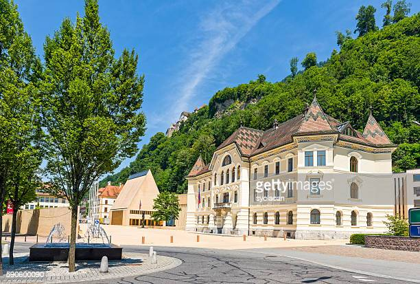 the parliament building with vaduz castle in liechtenstein - syolacan stock pictures, royalty-free photos & images