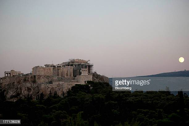 The Parthenon temple stands beneath a full moon on Acropolis Hill in Athens Greece on Tuesday Aug 20 2013 A third aid program for Greece announced by...