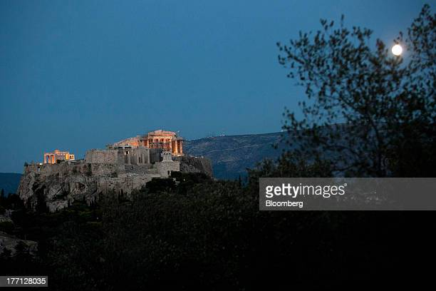 The Parthenon temple stands illuminated beneath a full moon on Acropolis Hill in Athens Greece on Tuesday Aug 20 2013 A third aid program for Greece...