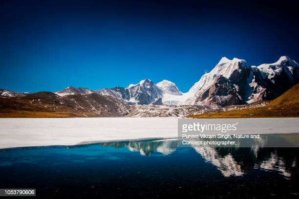 The Partially Frozen Gurudongmar Lake with reflection of the Mountains