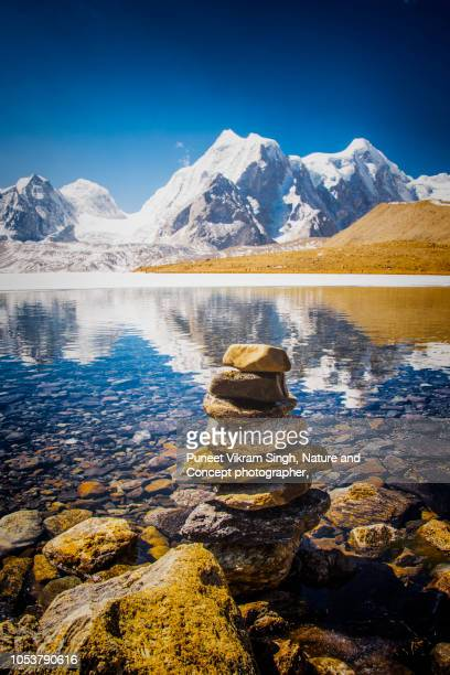 The Partially Frozen Gurudongmar Lake with stack of stones in foreground