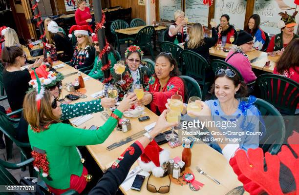 The participants in the 2nd Annual Ugly Christmas Sweater Bike Ride raise their glasses in a toast at the Longboards Restaurant Pub in dowtown...