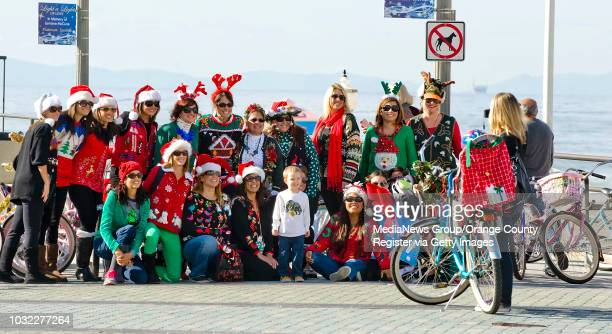The participants in the 2nd Annual Ugly Christmas Sweater Bike Ride pose for a photo on the Huntington Beach Pier Friday morning for the 2nd Annual...