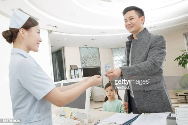the patient is at the cashiers desk - medical receptionist uniforms stock photos and pictures