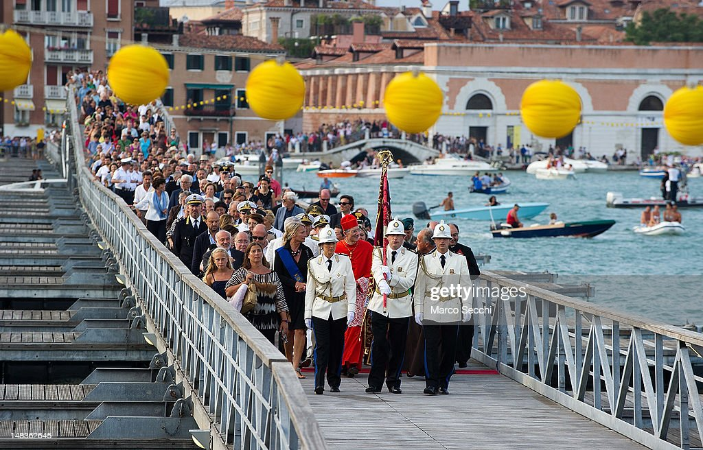 The Patriarch of Venice and authorities walk across the votive pontoon bridge across Giudecca Canal for the Redentore Celebrations on July 14, 2012 in Venice, Italy. Redentore is one of the most loved celebrations by Venetians which is in remembrance for the end of the 1577 plague. Highlights of the celebration include the pontoon bridge extending across the Giudecca Canal, gatherings on boats in the St Mark's basin and a spectacular fireworks display.