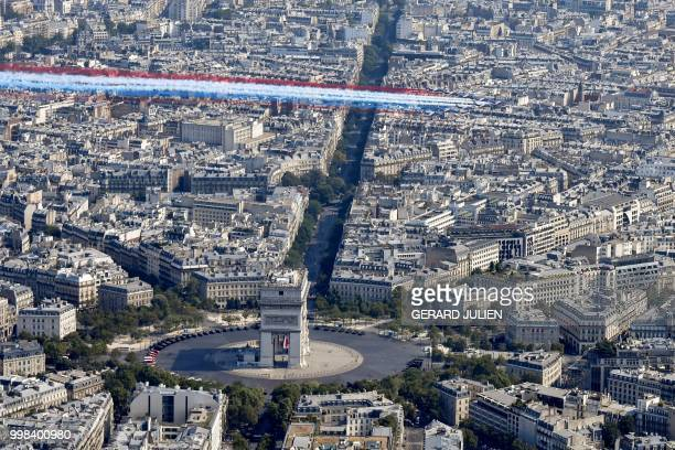 TOPSHOT The Patrouille de France Alpha Jet aircrafts fly over the Arc de Triomphe at the start of the annual Bastille Day military parade on the...