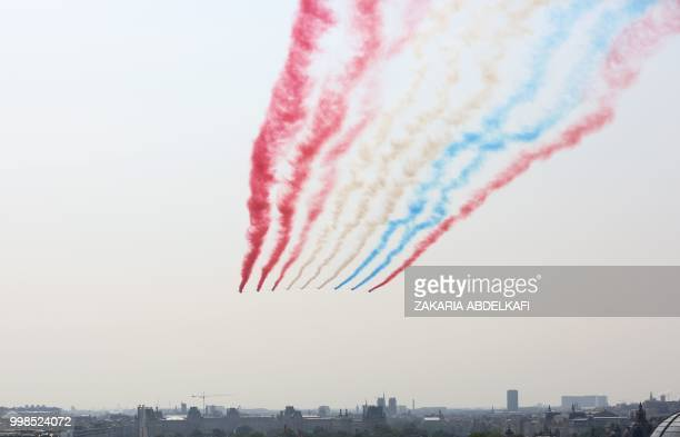 TOPSHOT The Patrouille de France Alpha Jet perform at the start of the annual Bastille Day military parade over the ChampsElysees avenue in Paris on...