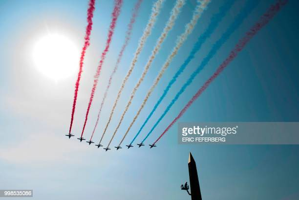 TOPSHOT The Patrouille de France Alpha Jets perform a flypast at the start of the annual Bastille Day military parade over the ChampsElysees avenue...