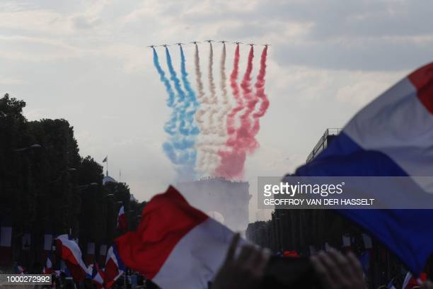 The Patrouille de France jets perform as they trail smoke in the colours of the French national flag while flying over the Arch of Triumph near the...